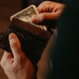 Hands pulling a dollar bill out of a leather wallet