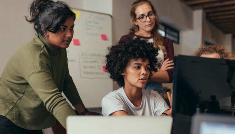 Group of businesswomen talk in front of a computer