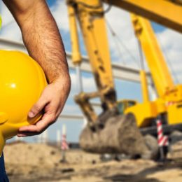 Construction worker stands with hardhat next to excavator
