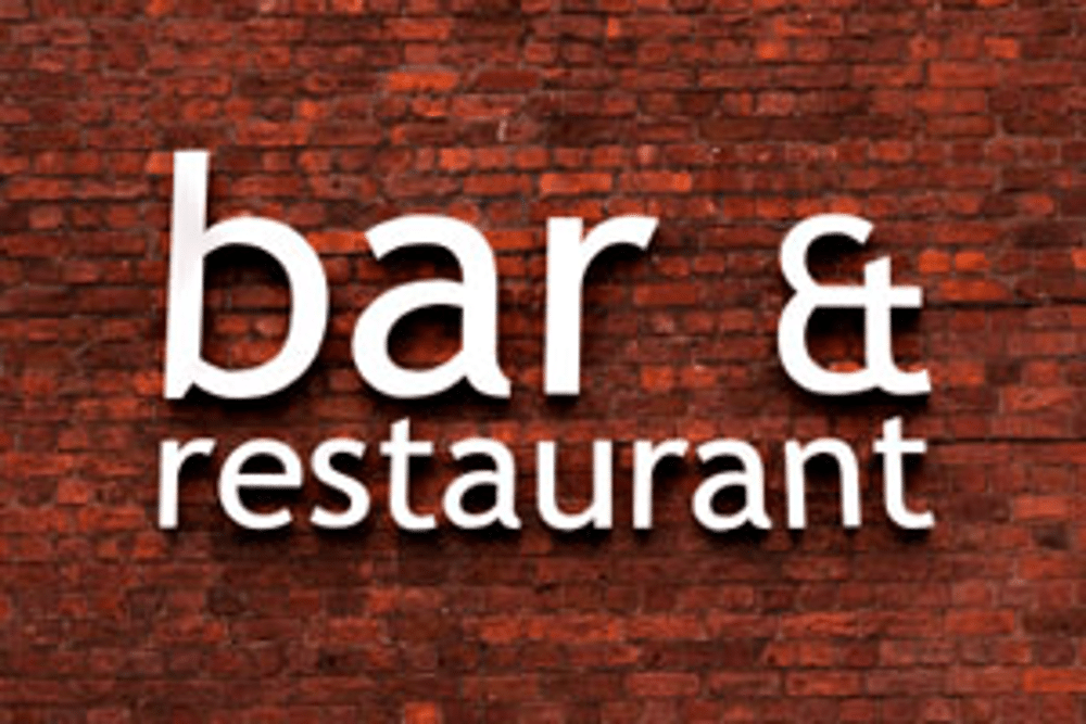 "The words ""bar & restaurant"" on a brick background"